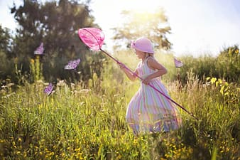 Girl in pink dress holding pink umbrella standing on green grass field during daytime