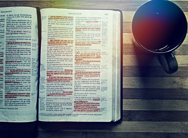 Opened bible book with highlighted verses beside black ceramic mug