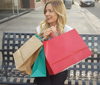Woman in white shirt holding paper bags