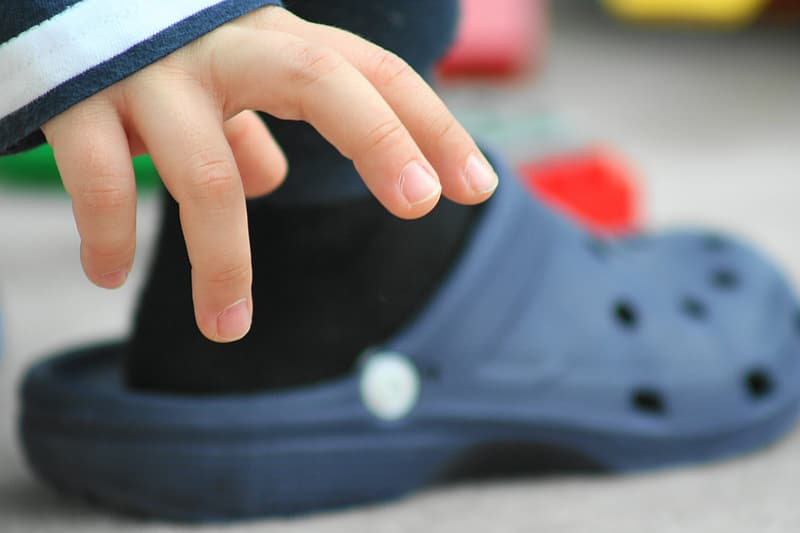 Person holding black and blue shoe