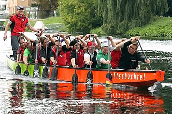 People on red boat rowing paddles
