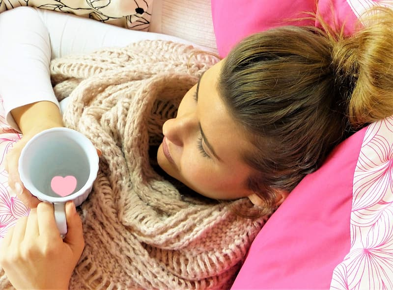 Blonde haired woman holding cup while lying on bed