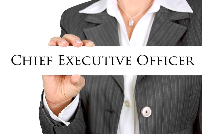 Woman in black and grey blazer holding Chief Executive officer sign