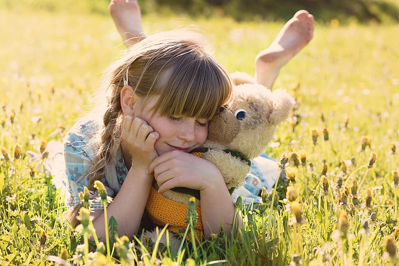 Girl with brown bear push toy smiling white lying on grass field