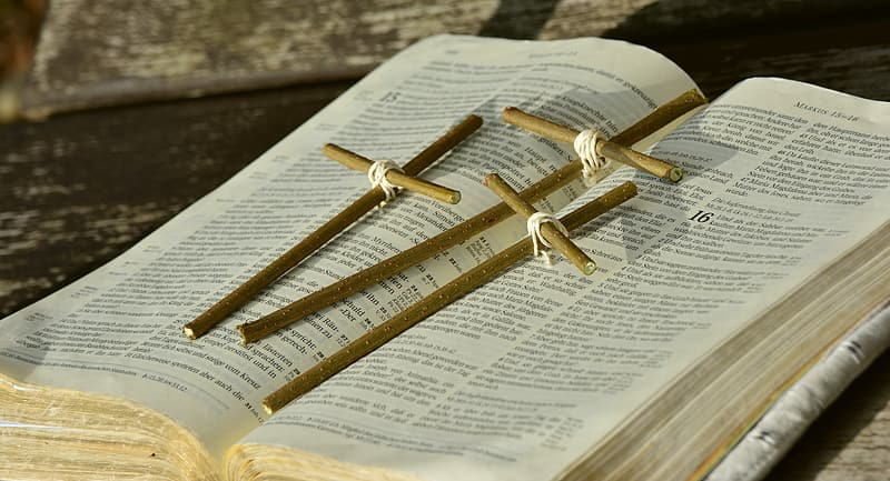 Three brown wooden cross on bible