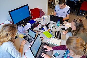 Group of four people gathered on a table using laptops