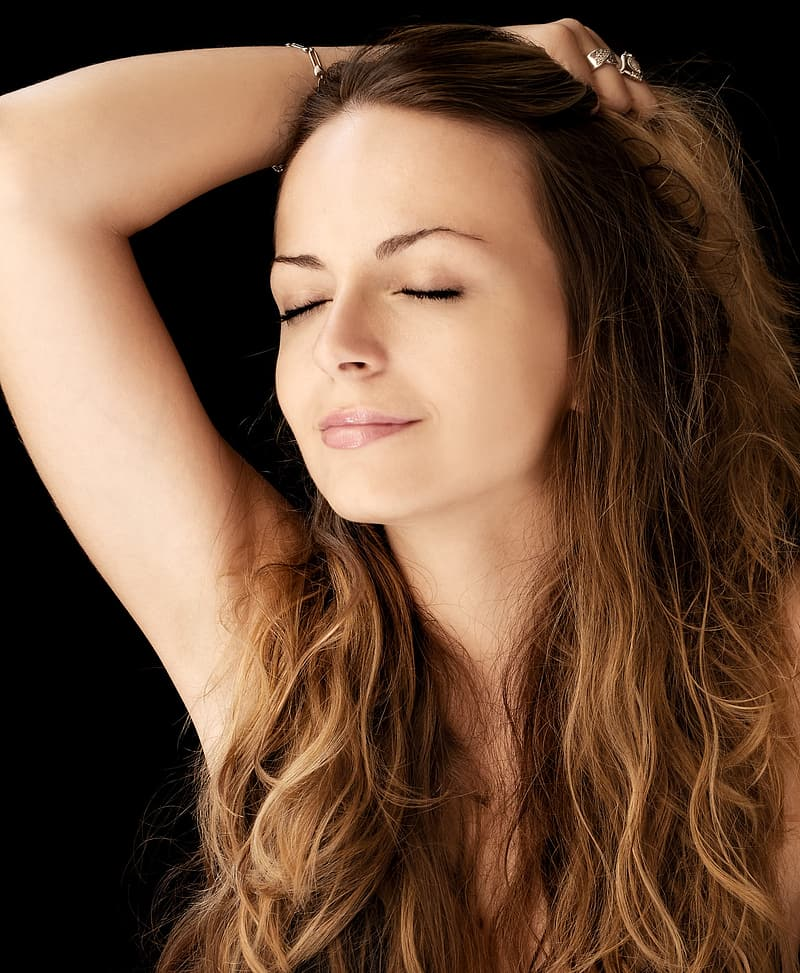 Woman with brown hair holding her hair