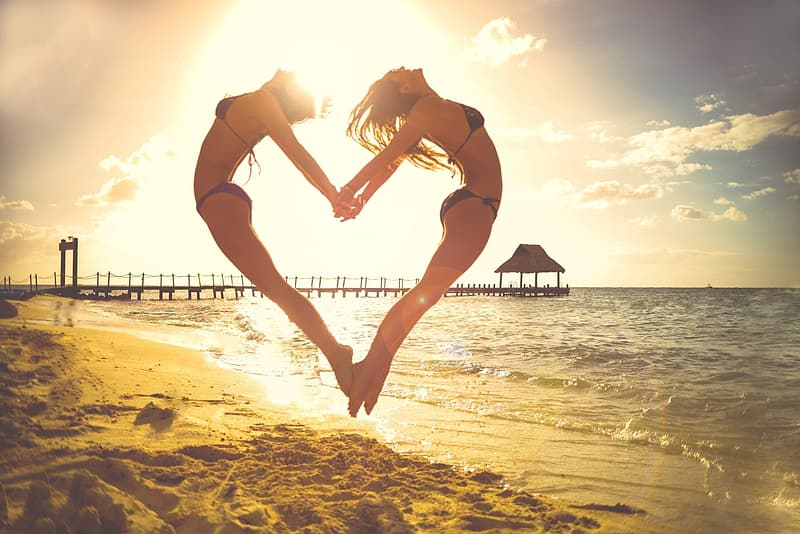 Two women jumping while forming heart shape beside seashore during daytime