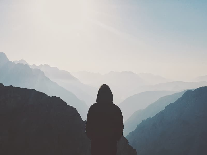 Silhouette person standing on mountain during daytime