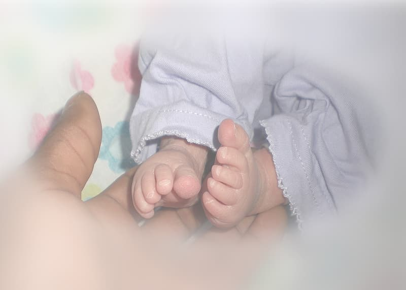 Person holding baby's feet