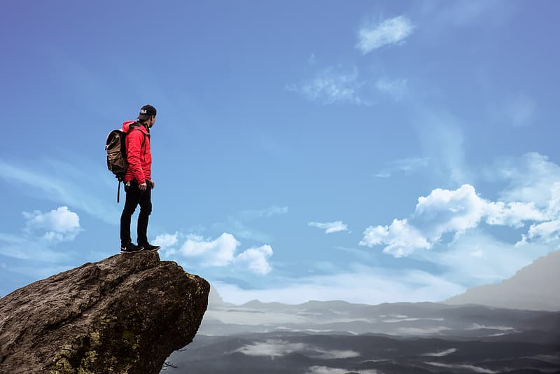 Man wears red jacket standing on rock formation at daytime