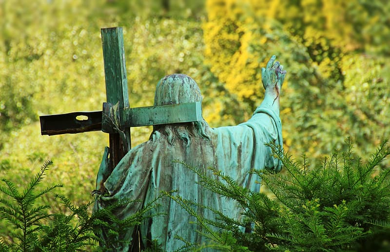 Christ carrying cross surrounded with grass statuette