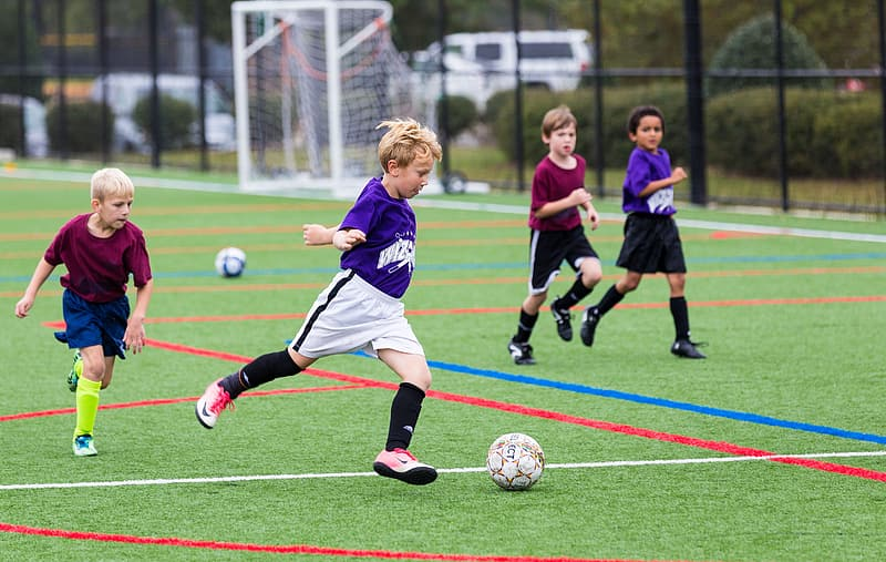 Boys playing soccer on field during day