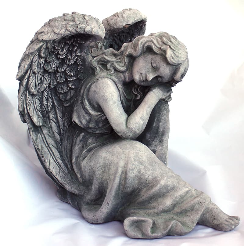 Close up photo of gray angel statuette on white textile