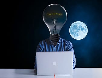 Person light-bulb head in front of silver MacBook with full moon background