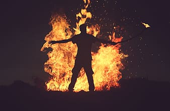 Silhoutte of man in front of bonfire