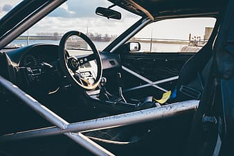 Closeup photography of vehicle interior with roll cage during daytime