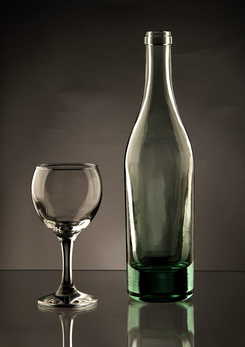 Clear wine glass and teal glass bottle