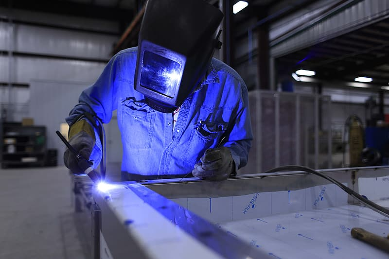 Welder wearing helmet and blue uniform