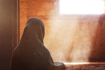Person with headscarf looking in the window wallpaper