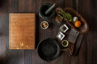 Black mortar and pestle near oval brown wooden bowl, and brown wooden cutting board