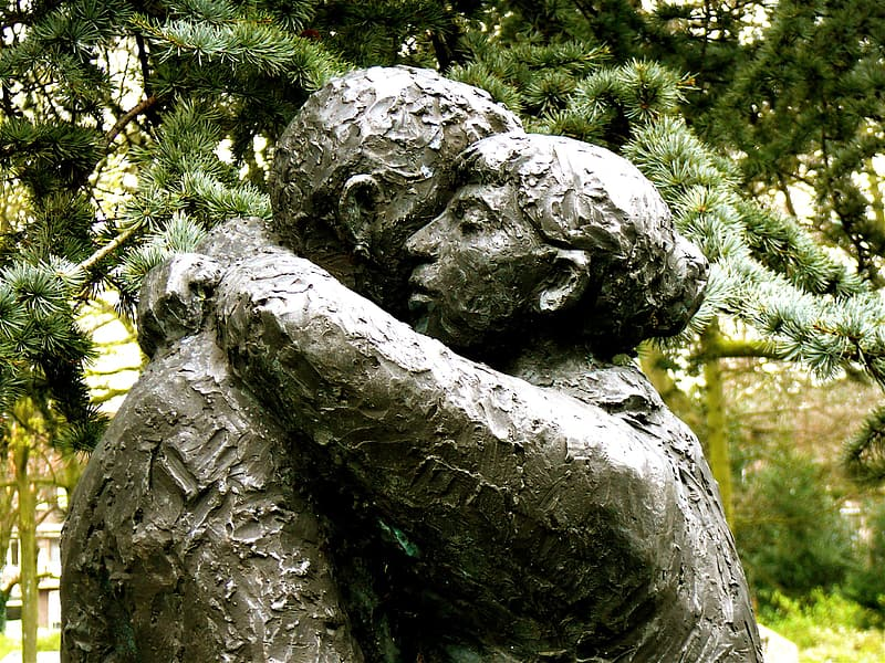 Man and woman hugging statue