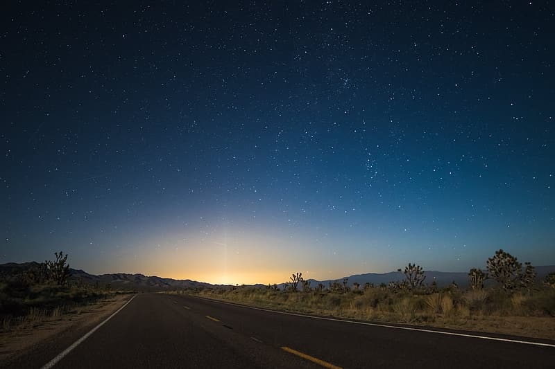 Time laps photo of star night sky to sunrise on asphalt road