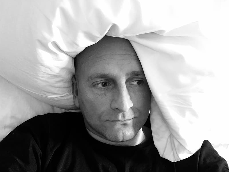 Grayscale photography of man lying on bed