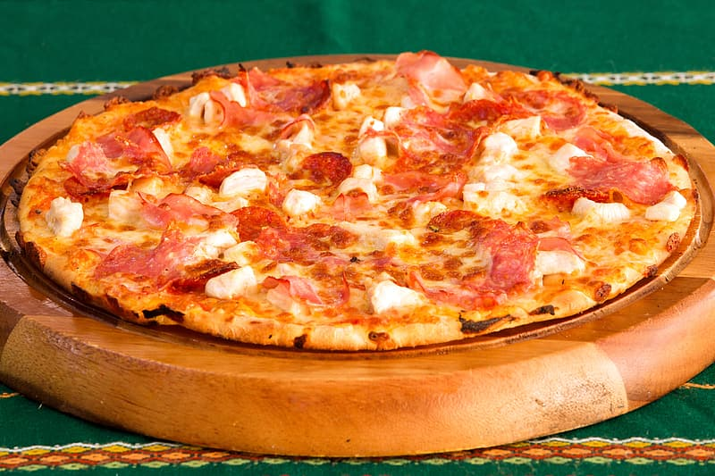 Pizza on brown wooden round tray