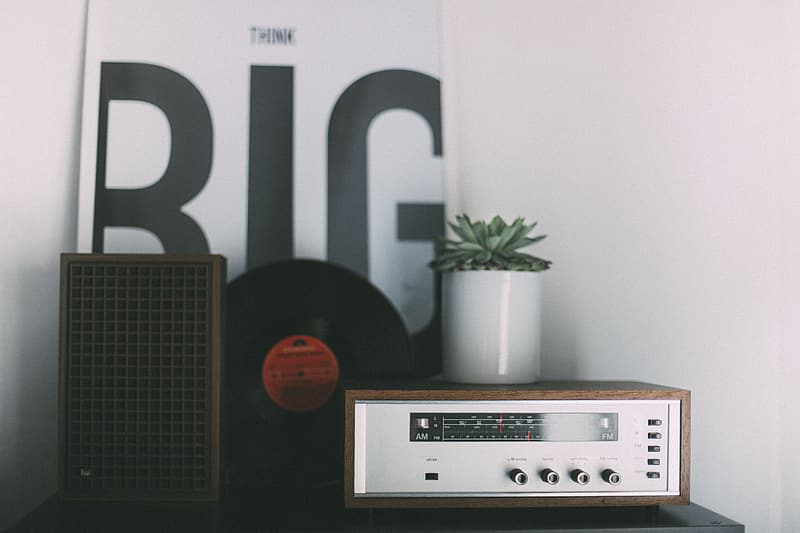 Gray and brown audio component beside speaker and vinyl record on table