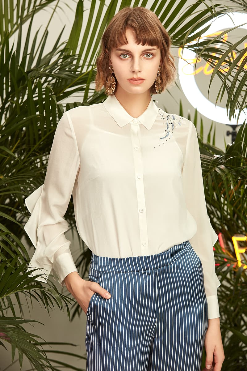 Woman in white dress shirt and blue and white striped skirt