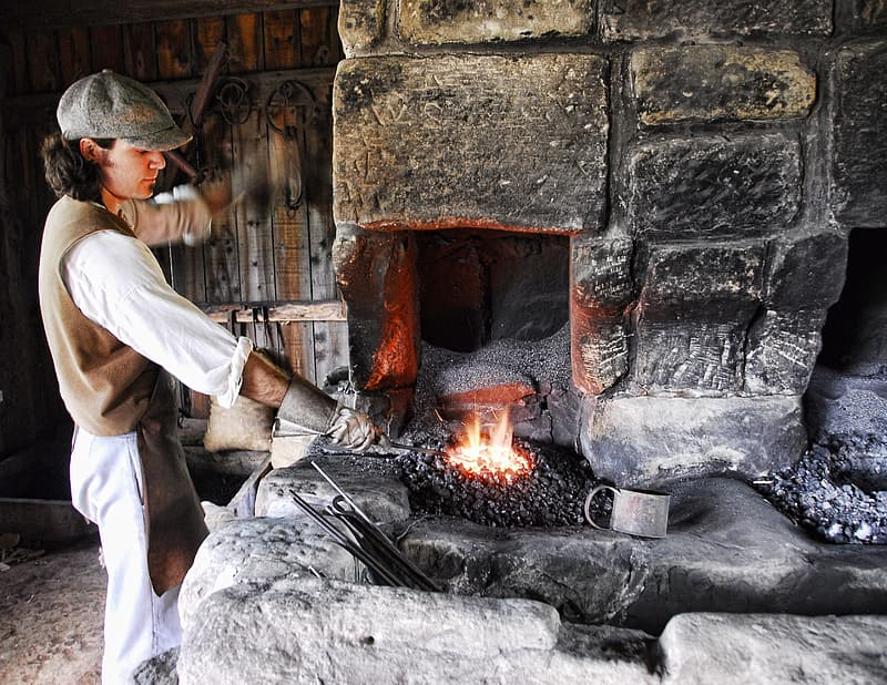 Blacksmith putting metal on fire