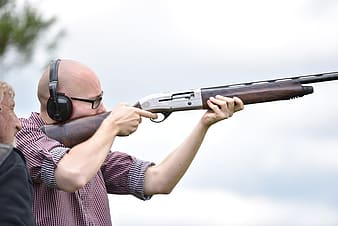 Person holds brown and gray shotgun