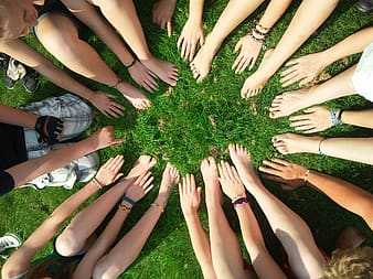 People hands and feet on green grass