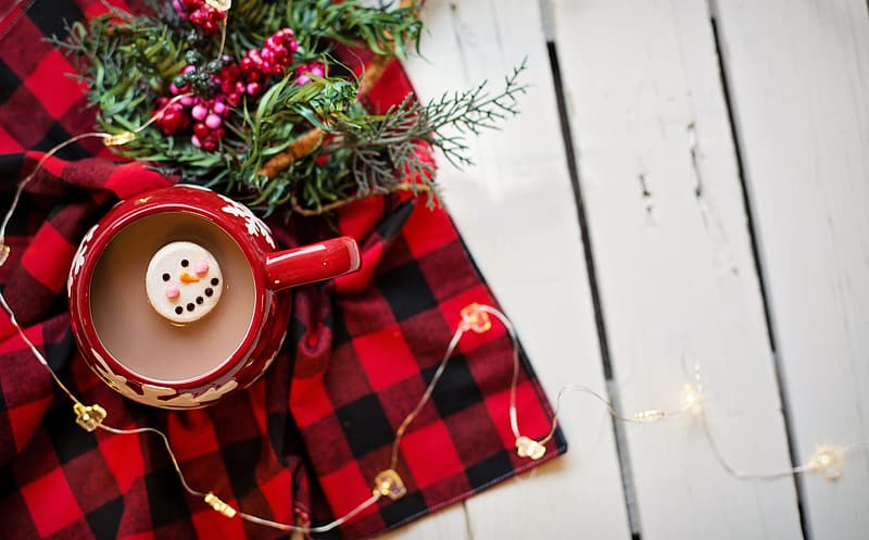 Red and white ceramic mug on red and black plaid textile