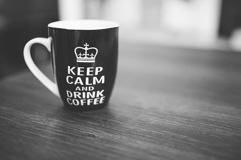 Black and white ceramic mug with keep calm and drink coffee print on gray surface