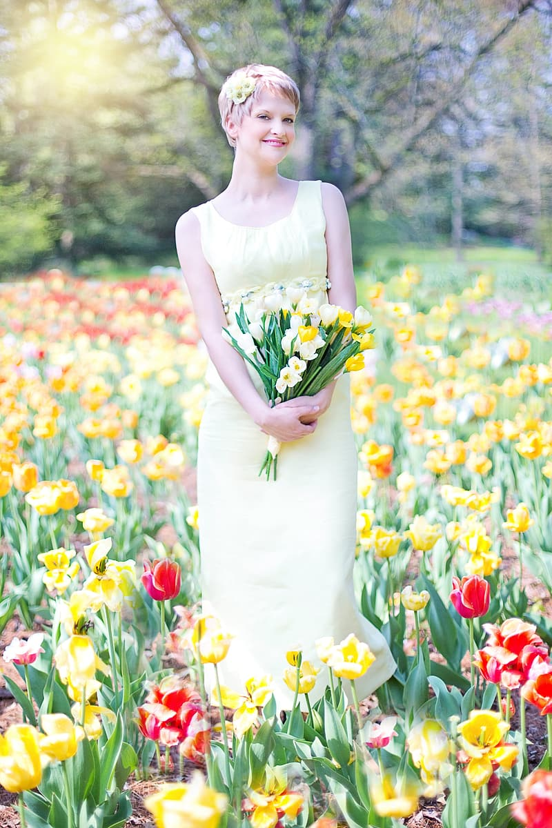 Photograph of woman wearing yellow dress on a bed of flowers