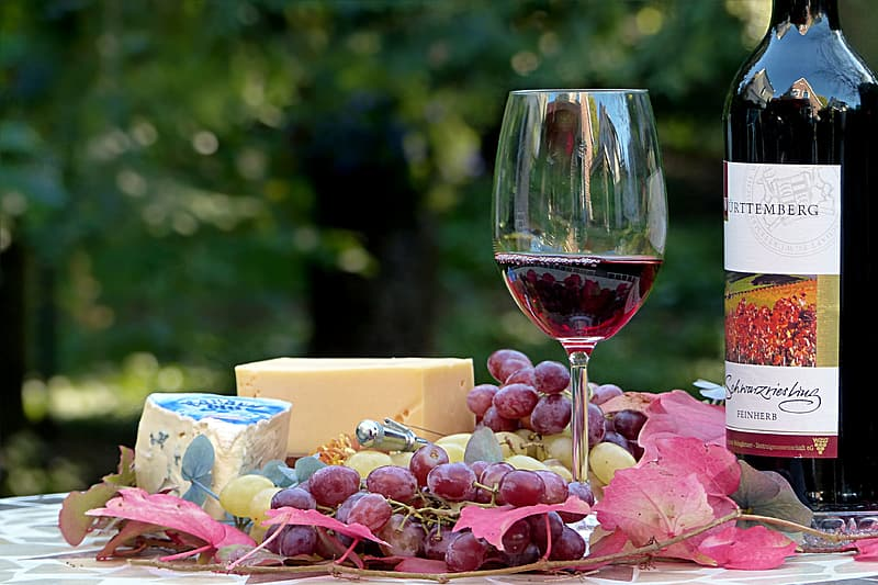 Grapes with wine glass and bottle on top of table