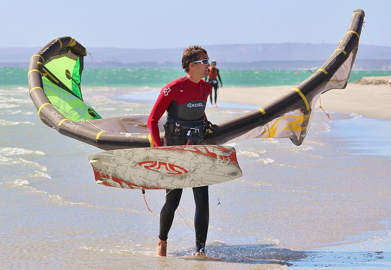 Person holding wakeboard and wind glider on beach shore