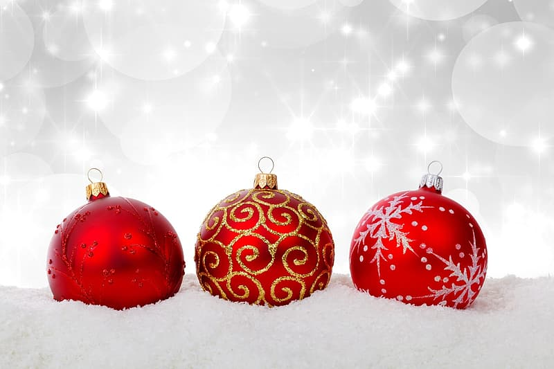 Selective color photography of three red glitter baubles on snow surface with lighted background