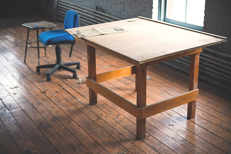 Brown wooden drafting table beside rolling chair
