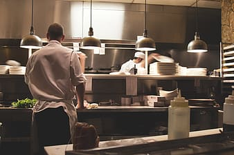 Man in chef uniform standing near counter