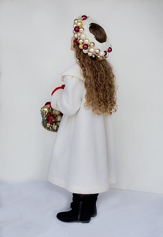 Girl with brown curly hair wearing white gown carrying basket full of bauble