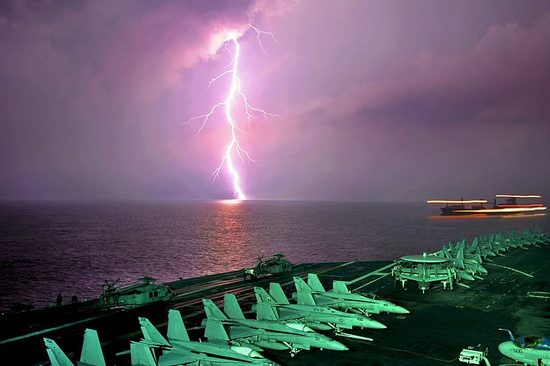 White fighter planes near lightning during night time