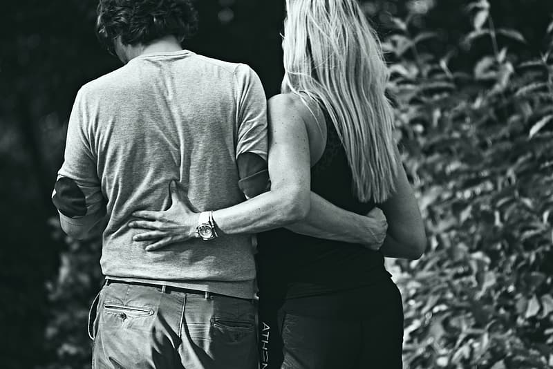 Grayscale photo of couple hugging