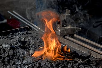 Charcoal with flame near black metal tool