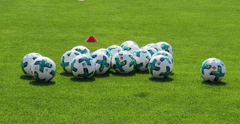 White-and-green soccer balls on field