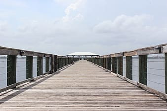 Brown wooden dock under white clouds during daytime