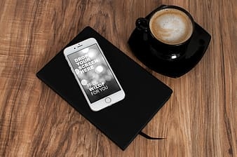 Silver iPhone 6 on top of black notebook near black ceramic coffee mug with saucer