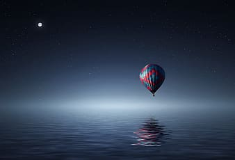 Red and blue hot air balloon over body of water at night time